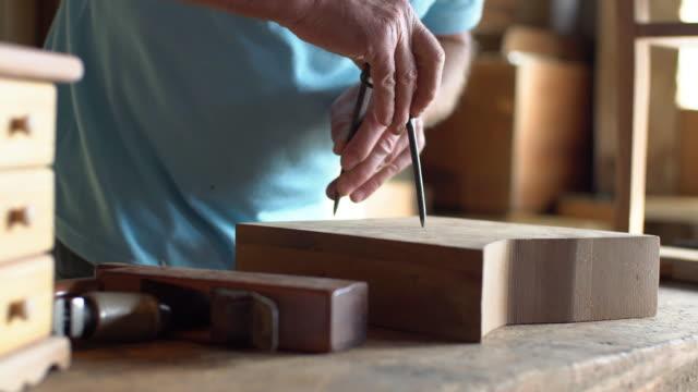 vídeos de stock, filmes e b-roll de desenho sênior do carpinteiro com um compasso - ferramenta de trabalho