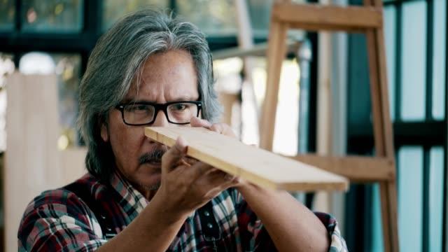 senior carpenter looking through to check wood - legno video stock e b–roll