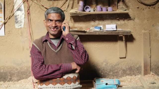 Senior carpenter on the phone at his workshop