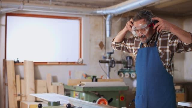 vídeos de stock e filmes b-roll de ds senior carpenter putting protective glasses and headphones on before working on the saw table - protetor de ouvido