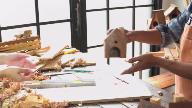 stockvideo's en b-roll-footage met senior carpenter stuurt zijn handgemaakte product als huis model naar de koper in het workshop huis - carving craft product