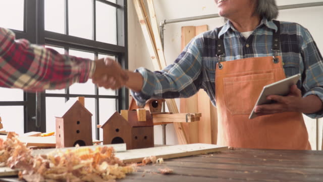 stockvideo's en b-roll-footage met senior timmerman schudt hand voor het succesvol verkopen van zijn handgemaakte product als huis model in de workshop huis - carving craft product