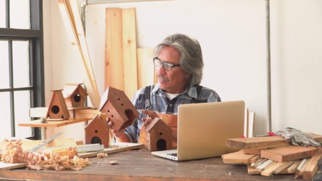 ワークショップハウスで彼の手作りの製品をハウスモデルとして販売するためのラップトップ上のシニア大工ストリーミング - 美術工芸品点の映像素材/bロール