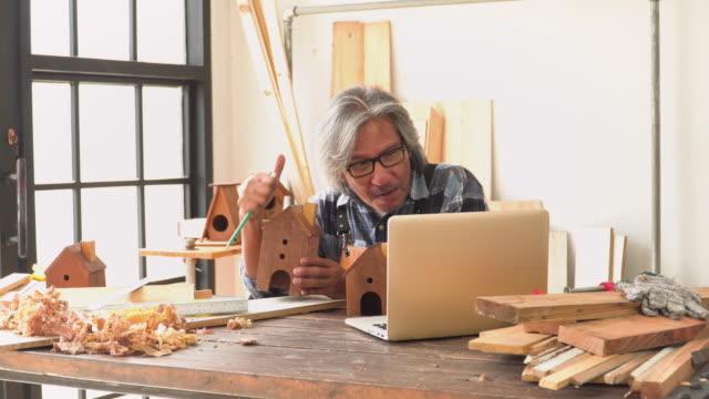 stockvideo's en b-roll-footage met senior carpenter streaming op laptop voor de verkoop van zijn handgemaakte product als huis model in de workshop huis - carving craft product