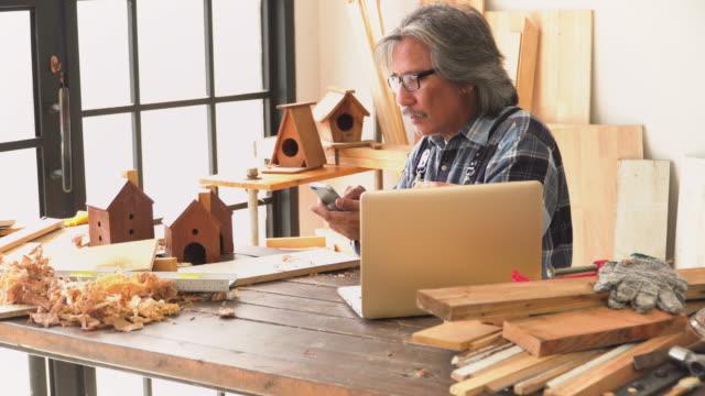 stockvideo's en b-roll-footage met senior timmerman het nemen van foto van zijn handgemaakte product als huis model te verkopen op sociale media in de workshop huis - carving craft product
