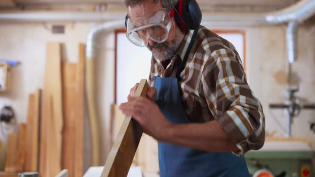 senior carpenter wearing protective wear in his workshop and checking a piece of wood he just cut - carpenter stock videos & royalty-free footage