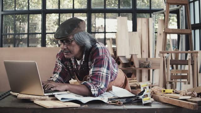 senior carpenter working with laptop - working seniors stock videos & royalty-free footage