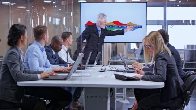 vídeos de stock e filmes b-roll de ds senior caucasian business man with grey beard holding a presentation using the display in the glass conference room - parte de uma série