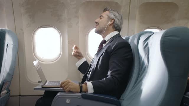 vídeos de stock, filmes e b-roll de empresário caucasiano sênior se divertindo com música durante o voo - primeira classe