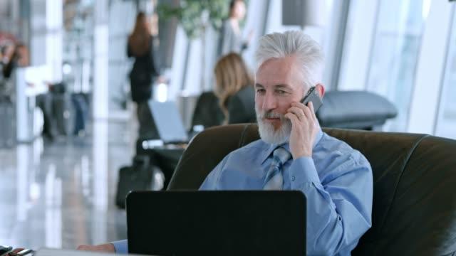 vídeos y material grabado en eventos de stock de empresario senior caucásica de ds hablar por teléfono mientras está sentado en el salón de negocios en el aeropuerto - usar el teléfono