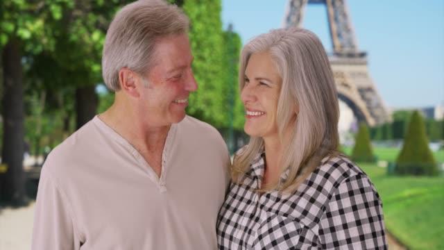 vidéos et rushes de senior caucasian couple stand together in front of eiffel tower - autre thème