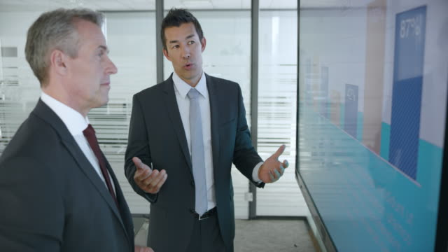 senior caucasian man and asian male colleague discussing the numbers shown in the financial presentation on the large screen in the meeting room - completo video stock e b–roll