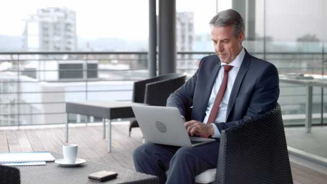 senior caucasian man sitting in the lounge on a terrace overlooking the city and working on his laptop - full suit stock videos & royalty-free footage