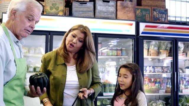 年配の白人のスタッフの違いを説明するスカッシュ、ヒスパニックの母と娘