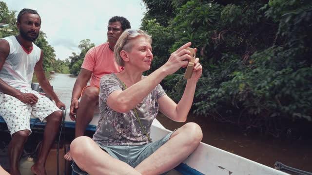 vídeos de stock, filmes e b-roll de mulher branca branca sênior, uma turista, acompanhada por dois guias locais tirando fotos com seu smartphone de um barco durante um passeio no rio bentota, sri lanka. - tourism