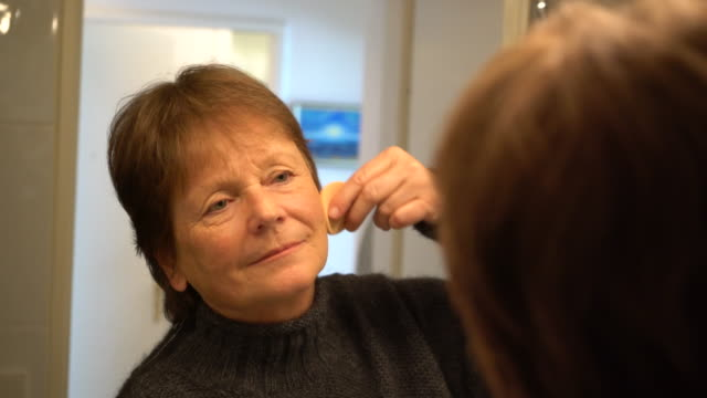 senior caucasian woman applying makeup in mirror - 70 79 years stock videos and b-roll footage
