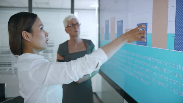 senior caucasian woman discussing the diagrams on the screen in meeting room with her asian colleague preparing for presentation - skill stock videos & royalty-free footage