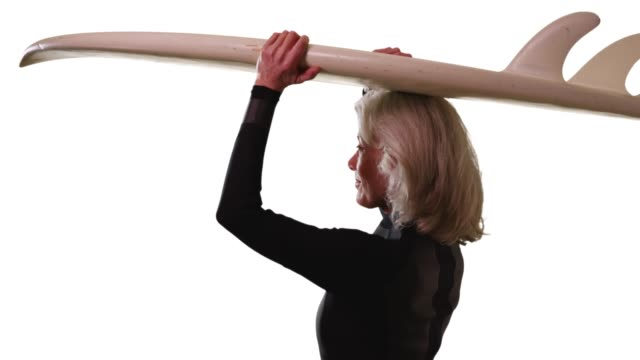 senior caucasian woman holding surfboard turning to smile at camera in studio - old diving suit stock videos and b-roll footage