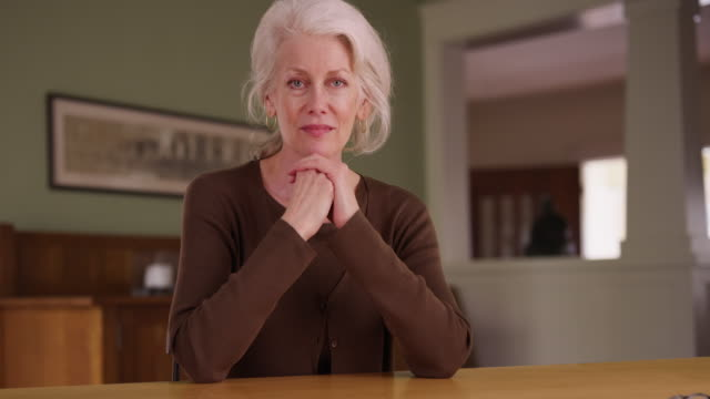 Senior Caucasian woman sitting at table in her home and looking at camera