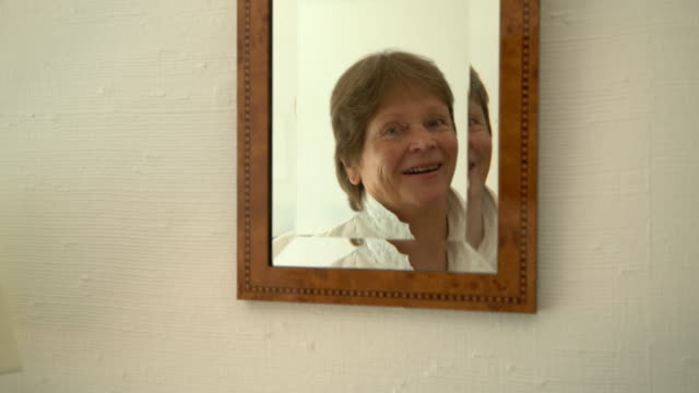 senior caucasian woman smiling in mirror - 70 79 years stock videos and b-roll footage