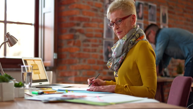 DS Senior Caucasian woman with glasses working in a startup office