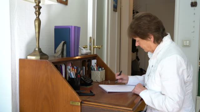 senior caucasian woman writing letter at desk - 70 79 years stock videos and b-roll footage