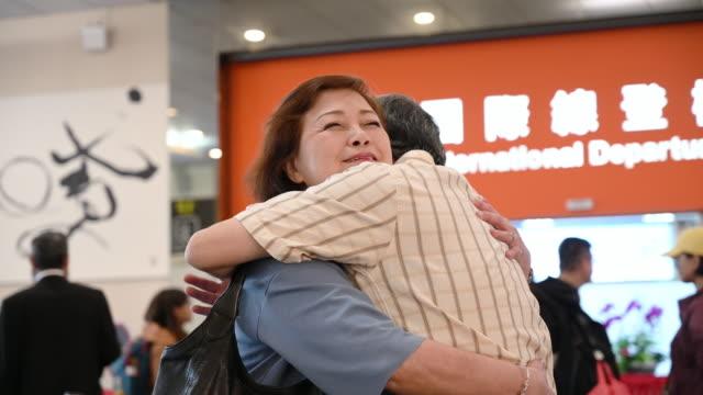 senior chinesisches paar umarmen sich bei flughafen-abflug - auseinander stock-videos und b-roll-filmmaterial