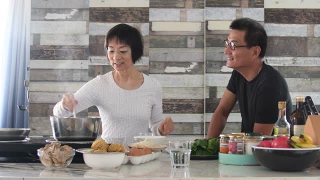 vidéos et rushes de couple chinois aîné faisant la nourriture ensemble et parlant - 60 64 ans