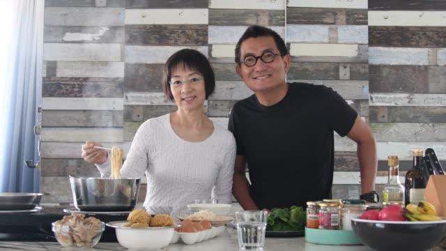 vidéos et rushes de couple chinois aîné préparant des nouilles et regardant l'appareil-photo - 60 64 ans