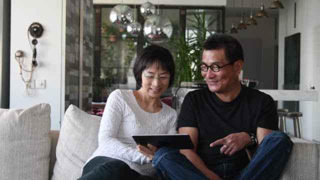 senior chinese couple watching tablet at home - usare un tablet video stock e b–roll