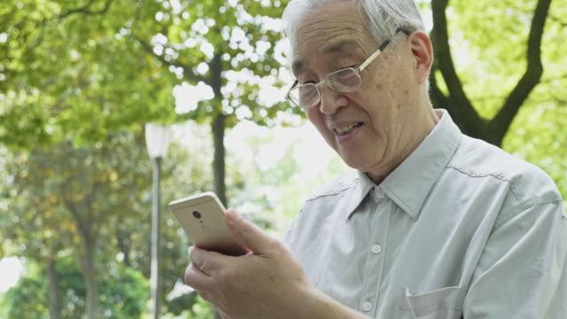 公園でスマートフォンを使う中国人男性 - china east asia点の映像素材/bロール