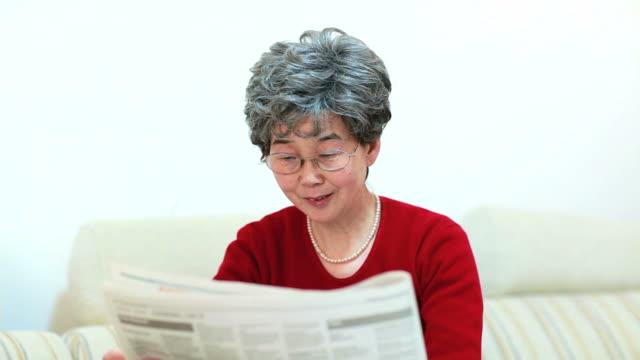 Senior Chinese woman reading newspaper