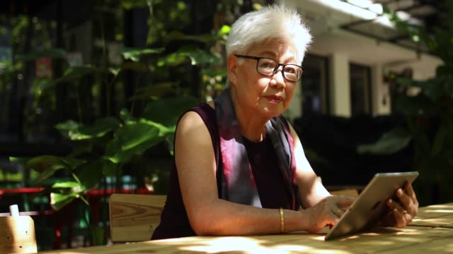 senior chinese woman using tablet - chinese ethnicity stock videos & royalty-free footage