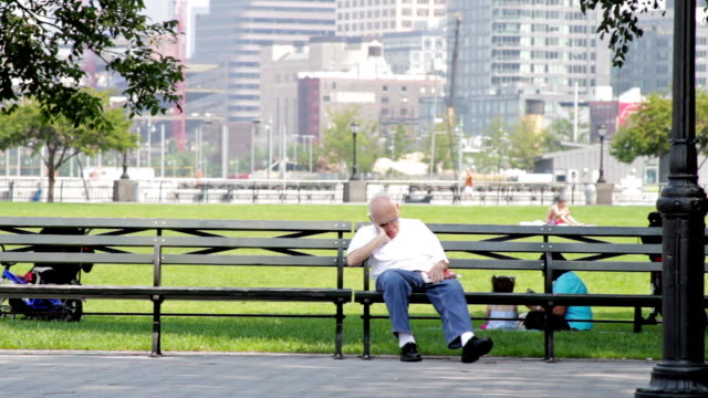 senior citizen sleeping on a bench at a park in new york city - bench stock videos & royalty-free footage