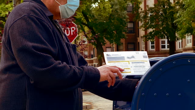 vidéos et rushes de senior citizen voter inserts his completed absentee ballot in a usps mailbox in chicago. donald trump has warned that mail-in voting will contribute... - united states postal service