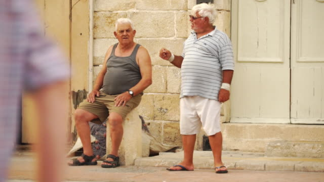 vídeos de stock e filmes b-roll de senior citizens having conversation in traditional village - malta - um dia na vida de