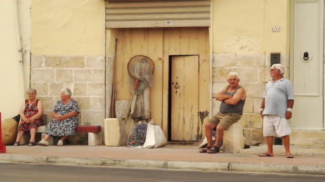 senior citizens having conversation in traditional village - malta - en dag i livet bildbanksvideor och videomaterial från bakom kulisserna