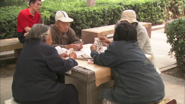 MS Senior citizens playing card game in outdoor park, Beijing, China