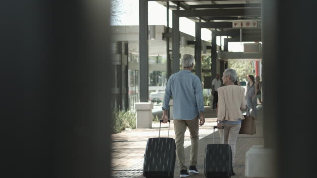 vidéos et rushes de senior citizens walking with suitcases, medium shot - valise