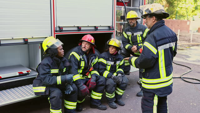 senior company officer talking with fire crew on location - resting stock videos & royalty-free footage