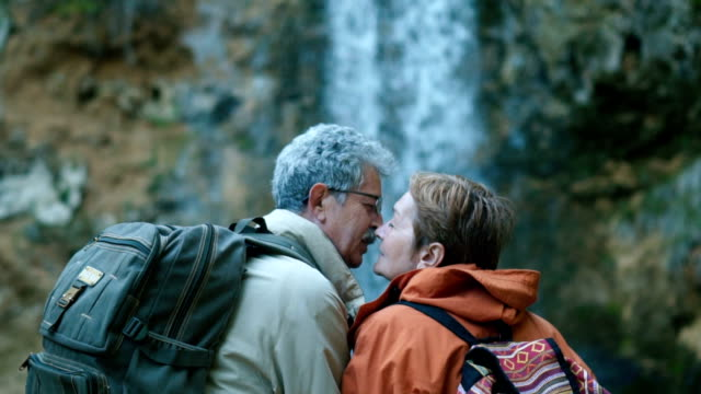senior couple admiring beautiful waterfall - senior couple stock videos & royalty-free footage