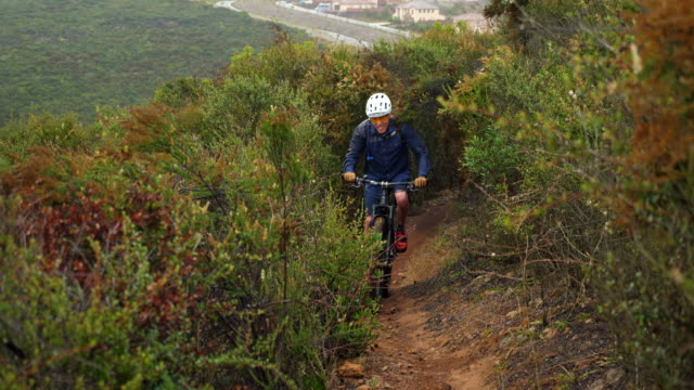 vidéos et rushes de ms senior couple and friends riding mountain bikes on trail through lush hillside above city - faire du vélo tout terrain