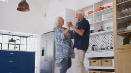 Senior Couple At Home Dancing In Kitchen Together