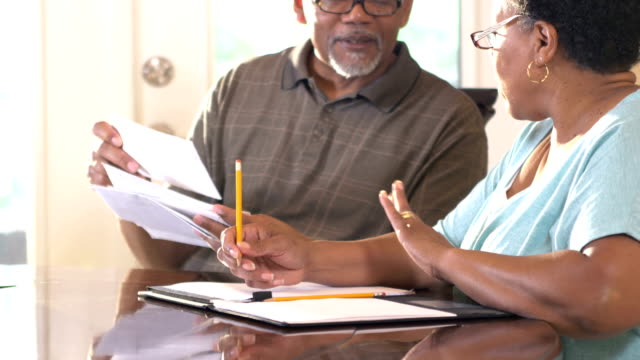 senior couple at home paying bills - home finances stock videos & royalty-free footage