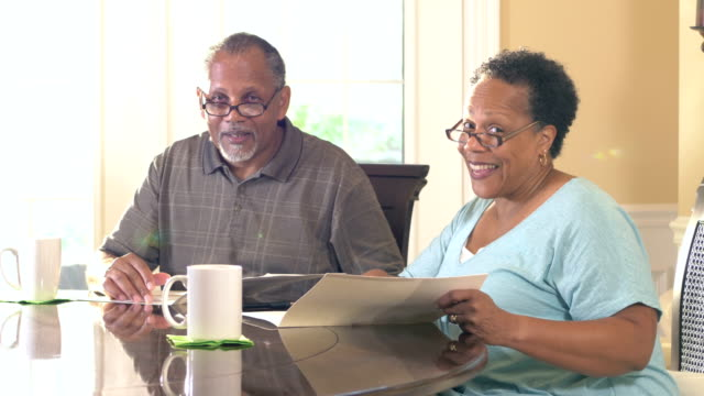 senior couple at home reading brochure, smiling - brochure stock videos and b-roll footage