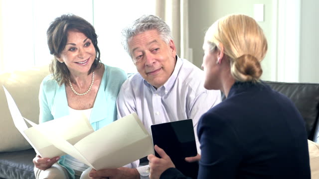 Senior couple at home talking to financial planner