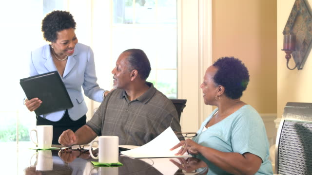senior couple at home with financial advisor - brochure stock videos & royalty-free footage