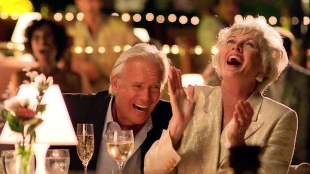 ms senior couple at table watching performance off camera laughing + clapping - dining stock videos and b-roll footage