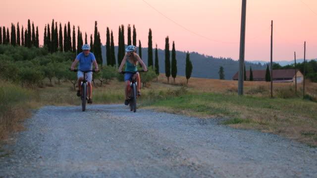 coppia senior in bicicletta la sera d'estate - stagione video stock e b–roll