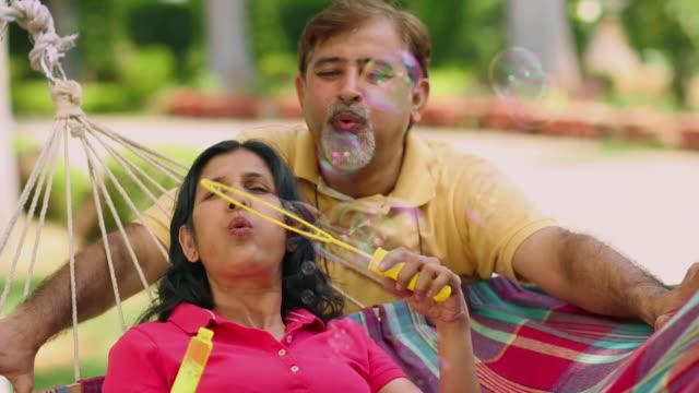 Senior couple blowing bubble wand, Delhi, India